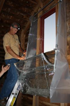 Image of Mick Valent and the team set up a harp trap to catch bats as they exit the barn loft at dusk.