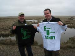 Image of Gene Muller, President of Flying Fish Brewing Company and David Wheeler, Executive Director of Conserve Wildlife Foundation hold up F.U. Sandy shirts.